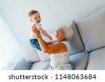 senior woman hold little baby... | Shutterstock . vector #1148063684