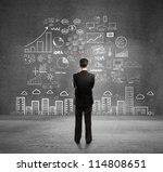 businessman with business plan concept on wall - stock photo