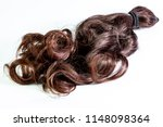 A set of hair extensions of reddish brunette curly hair on a beauty shop table