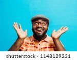 Small photo of It's incredible! Portrait of a happy and excited man looking up with mouth open and both arms up