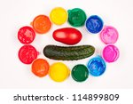 motley paints on the white background with vegetables. paints arranged in rainbow oval ring with tomato and cucumber in the center. studio shot - stock photo