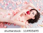 beautiful  nude woman with roses eating an apple - stock photo