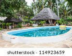 Kenya. Luxury swimming pool in African garden with tipical local chairs made of wood  on background