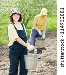 Two women fertilizes the soil in garden - stock photo