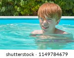 Headshot of a ginger haired teenage boy in a swimming pool - stock photo
