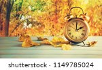 Clock And Leaves On Wooden...