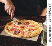 men's hands cut the pizza into... | Shutterstock . vector #1149893264