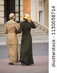 Two beautiful slim girls in costumes. walking along cobbled street of old european town. Old-fashioned retro novel