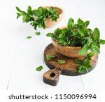 bowl with fresh mint on a old... | Shutterstock . vector #1150096994