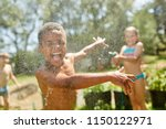 african boy is splashed by girl ... | Shutterstock . vector #1150122971