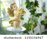 Statuette Of Cupid Holding A...