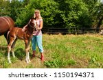breeder with a 3 weeks old foal | Shutterstock . vector #1150194371