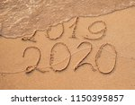 Small photo of New Year 2020 is coming concept - inscription 2019 and 2020 a beach sand, the wave is almost covering the digits 2019