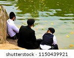3 Jew Hasidic boys, , a family of Hasidic Jews, in traditional black clothes  sitting near the lake in Uman,Ukraine, the time of the Jewish New Year,  Orthodox religious  Jews