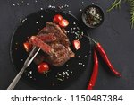 rare rib eye steak on dark... | Shutterstock . vector #1150487384