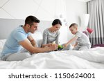 Stock photo people family and morning concept happy child with toy tractor and parents playing in bed at 1150624001