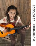 young girl playing the guitare - stock photo