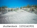 grassy windy sand dunes on the... | Shutterstock . vector #1151161931