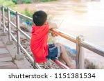 kid boy sit on the iron balcony ... | Shutterstock . vector #1151381534