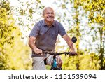 joyful senior man riding a bike ... | Shutterstock . vector #1151539094