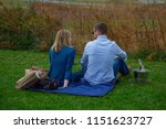 Small photo of Charlottesville, Virginia, USA - November, 19, 2016: Young Couple enjoining picnic with Wine bottle on green field during the fall (autumn) season.