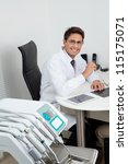 Portrait of a happy young male dentist sitting at office desk - stock photo