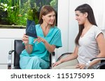 Female dentist with woman examining dental X-ray in clinic - stock photo