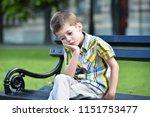 sad child boy sitting on a bench   Shutterstock . vector #1151753477