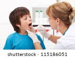 Doctor consulting a young boy - sore throat concept - stock photo