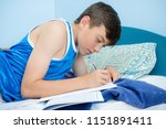 Caucasian teenage boy laying on his bed doing homework - stock photo