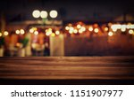 Stock photo image of wooden table in front of abstract blurred restaurant lights background 1151907977