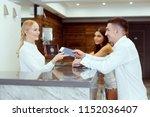 couple near reception desk in... | Shutterstock . vector #1152036407