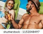couple clinking with bottles of ... | Shutterstock . vector #1152048497