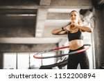 Small photo of Beautiful caucasian young woman doing hula hoop in step waist hooping forward stance. Young woman doing hula hoop during an exercise class in a gym. Healthy sports lifestyle, Fitness, Healthy concept.