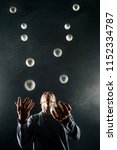 Small photo of Blond juggler with white balls on black background