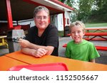 father and son at a fair eating ... | Shutterstock . vector #1152505667