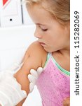 Little girl getting an injection or vaccine - closeup - stock photo