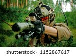 Small photo of Airsoft man with optical sight gun. Soldier hidden into spruce branches on forest territory