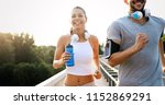 athletic couple jogging together | Shutterstock . vector #1152869291