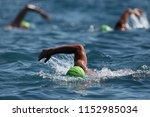 three swimmers swim in the... | Shutterstock . vector #1152985034