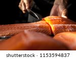 Stock photo the big salmon is in the hands of the experienced japanese chef he is using a knife to slice 1153594837