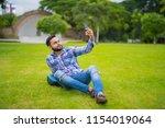 handsome indian man in park... | Shutterstock . vector #1154019064