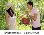 The man with the shopping cart offers the woman apple - stock photo