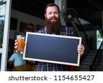 bearded business owner standing ... | Shutterstock . vector #1154655427