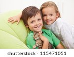 Happy kids with their new pet - a little tired kitten - stock photo