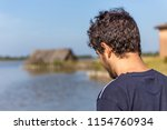 boy in front of old cabin on... | Shutterstock . vector #1154760934