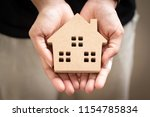 Small photo of Hand holding home model, happy homes for families.