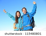 Happy hiking couple cheering in winning success concept. Young woman and man hiker holding around eachother elated and cheerful with arms raised in the sky. Asian girl and Caucasian male hikers. - stock photo