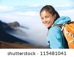 Hiker portrait of young woman hiking in high mountains. Beautiful blissful serene smiling happy mixed race Asian / Caucasian woman outdoors in big nature. - stock photo