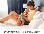 young mother  sitting in bed... | Shutterstock . vector #1154826094